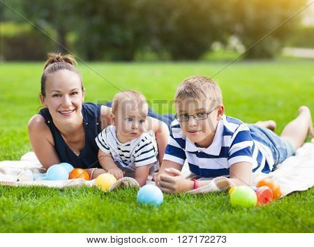 Happy mum and her children playing in park together. Outdoor portrait of happy family