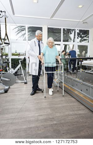 Physiotherapist Assisting Woman With Walker In Rehab Center