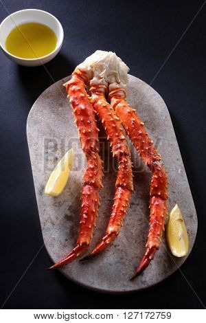 Red king crab legs with lemon on a marble cutting board