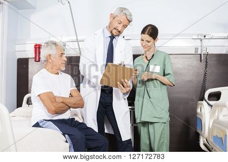 Doctor And Nurse Communicating Over Report By Senior Patient