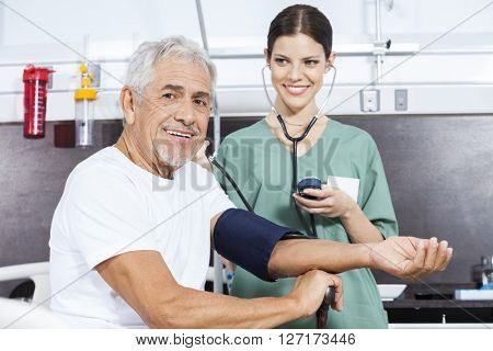 Young Nurse Checking Blood Pressure Of Senior Patient