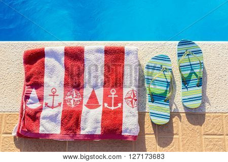 Bathing slippers and bath towel at blue swimming pool in summer