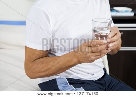 Midsection Of Patient Holding Water Glass In Rehab Center