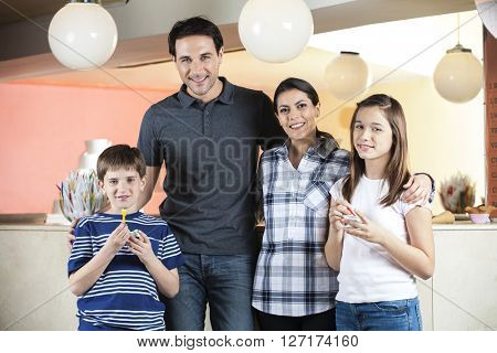 Happy Family Standing In Ice Cream Parlor