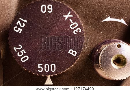 Fragment of old film camera. Top view dial of exposure and shutter button. Close up view. Macro. Selective focu. sVintage photo. Toning.