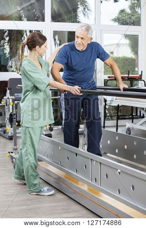 Female Physiotherapist Motivating Senior Man To Walk Between Par