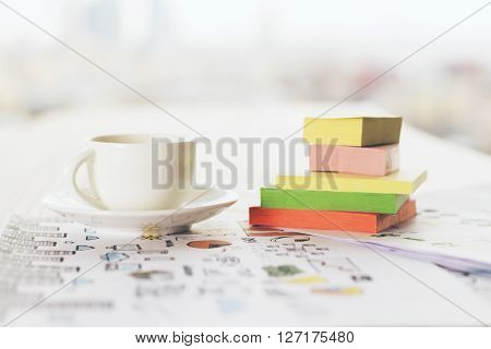Frontview of coffee cup and colorful stickers on business concept sketch