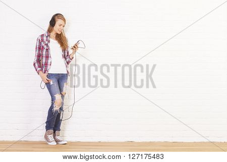 Casually dressed caucasian female listening to music in studio with white brick wall and wooden floor. Mock up