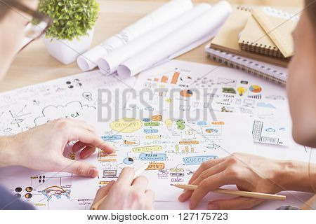 Rearview of businesspeople discussing business sketches on desktop with plant and spiral notepads