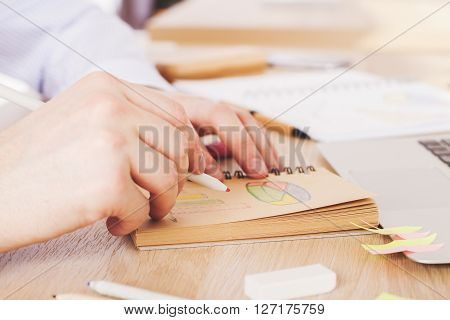 Sideview of male hand drawing business diagrams on wooden desktop
