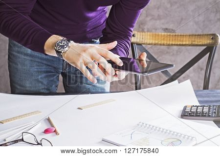Male hands using digital tablet above desktop