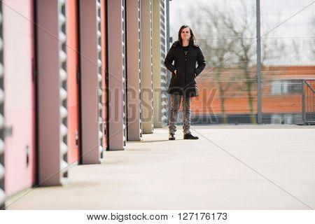 Feminine Man Standing Next To Industrial Garages