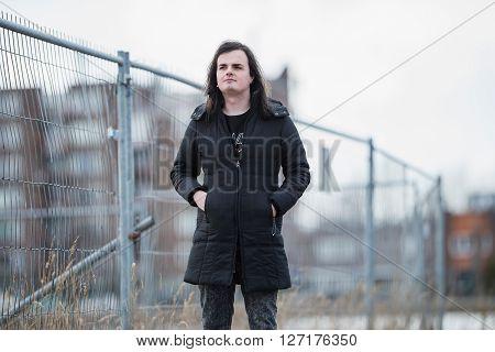 Feminine Man In Industrial Area Near Fence