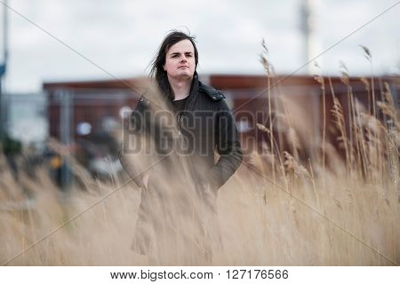 Androgynous Man In Field Of Reed In Industrial Area