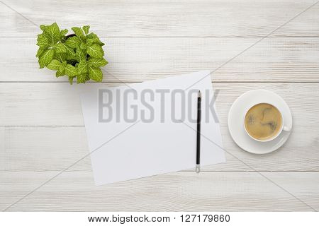 Office workplace with green houseplant, cup of coffee and white paper with pencil in top view. Increasing productivity in the mornings. Keeping healthy. Contribution to wellbeing. Reducing stress. Improving mood and productivity.