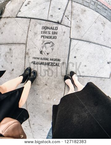 APRIL 24, 2016 LOS ANGELES, CA - Fisheye lens perspective of spray painted artwork on sidewalk depicting local community's disdain for presidential candidate Donald Trump on sidewalk in Downtown LA. Translation: