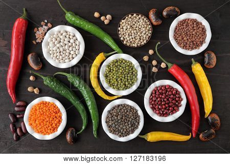 Colorful beans and lentils in ceramic bowls on a dark background.