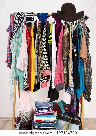 Many colorful clothes on hangers in a store. A lot of clothes and accessories hanging on a rack nicely arranged on hangers and in piles.