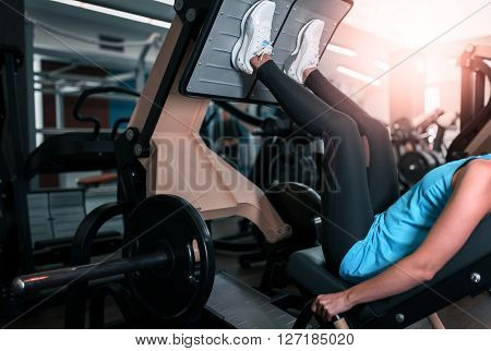 Woman working exercise on training apparatus in club