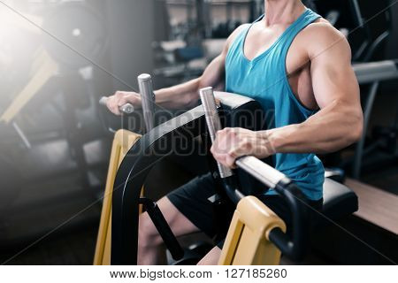Man Working On Fitness Machine At Gym