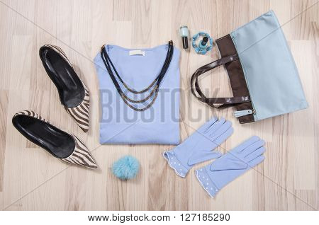 Winter sweater and accessories arranged on the floor. Woman blue and brown accessories high heels necklace and gloves lied down.