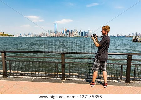 NEW YORK AUGUST 24: A man taking photos from the Manhattan skyline New York August 24 2015. This view is from the Liberty Island where the Statue of Liberty stands.