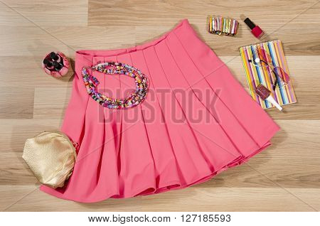 Pink pleated skirt and accessories arranged on the floor. Woman skirt with accessories purse sunglasses bracelets and nail polish.