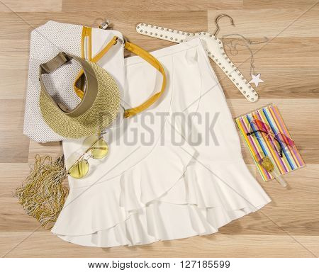 White skirt with ruffles and accessories arranged on the floor. Woman skirt with accessories purse sunglasses visor and nail polish.