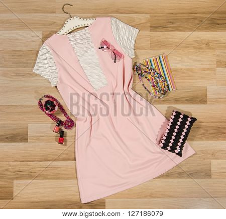 Pink pleated skirt and accessories arranged on the floor. Woman dress with accessories purse heart sunglasses and necklace.