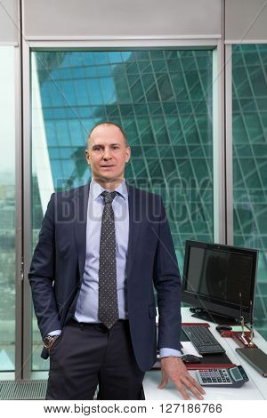 Portrait of a successful businessman in a suit inside the office building