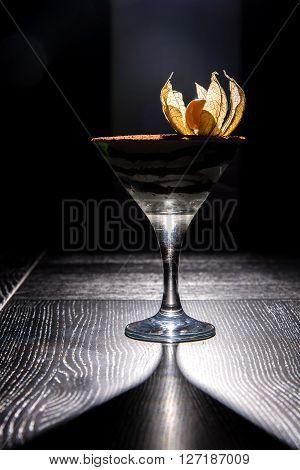 tiramisu dessert in glass on black wooden table