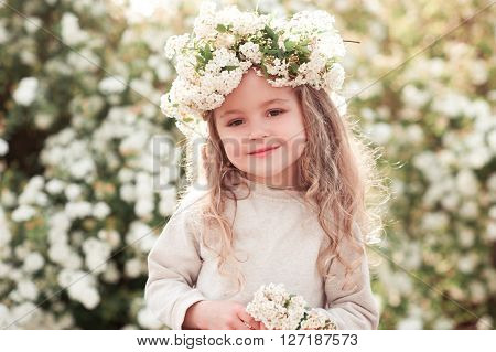 Smiling kid girl 3-4 years old posing over floral background. Wearing flower wreath outdoors. Looking at camera. Childhood.