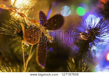 Dragonfly toy on christmas tree with magic lights