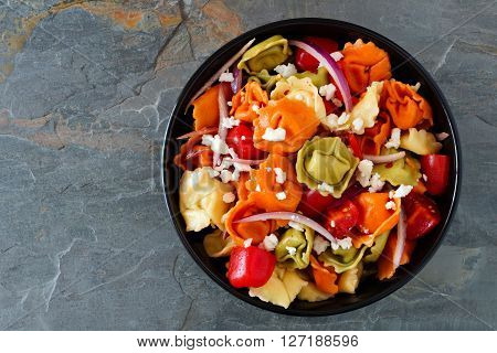 Colorful Tortellini Pasta Salad With Tomatoes And Onions, Overhead View On A Dark Slate Background