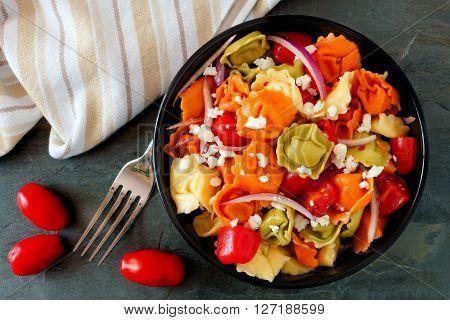 Colorful Tortellini Pasta Salad With Tomatoes And Onions, Overhead Scene On Dark Slate