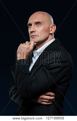 Pensive mature businessman standing on dark background