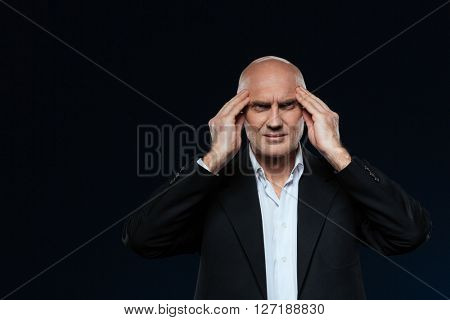 Mature businessman with headache standing over black background