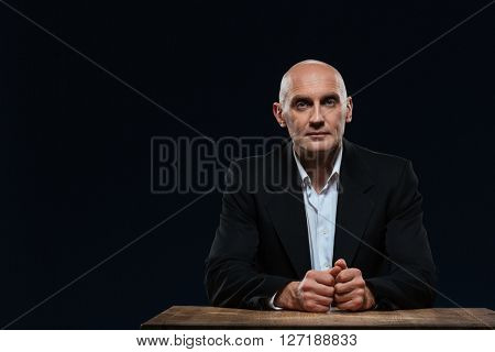 Mature businessman sitting at the table and looking at camera over black background