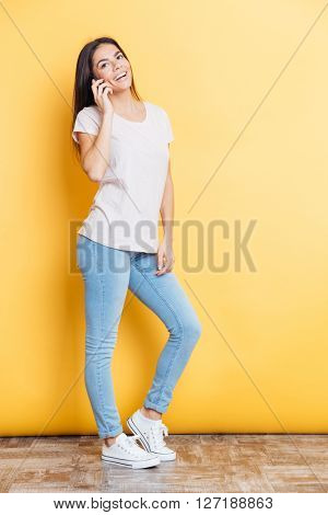 Full length portrait of a smiling woman talking on the phone over yellow background