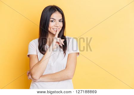 Pretty woman showing finger over lips on yellow backgound