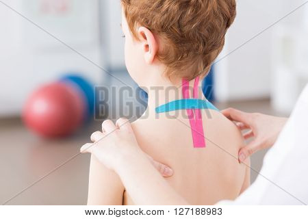 Little crooked boy with spine problems having kinesiotaping on his cervical spine. Physiotherapist exercising with little patient