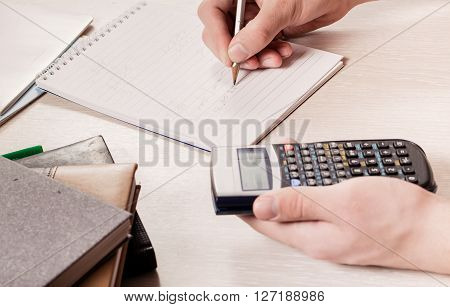 The hands of the person holding the calculator and a pencil. Calculation of people writes down results in a notebook. Close up