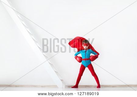 Super Hero Boy In Red Boxing Gloves And A Cape In The Wind.