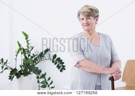 Positive senior woman with walking stick standing in light interior
