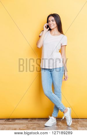 Full length portrait of a happy woman talking on the phone and looking away over yellow background