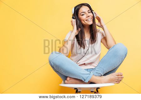 Smiling woman sitting on the chair with headset over yellow background