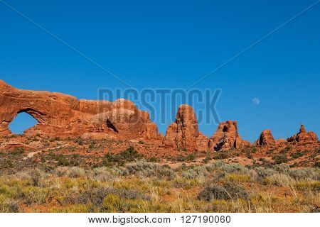 a full moon rising over the scenic arches national park landscape and turret arch