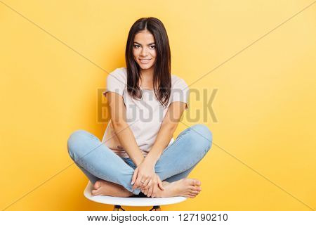 Smiling lovely woman sititng on the chair over yellow bakground and looking at camera