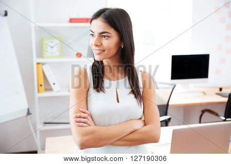 Happy businesswoman standing with arms folded in office
