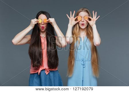 Two funny amazed cute young women with long hair covered their eyes with marmalade candies over grey background